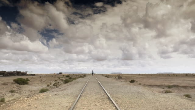 Man walking over the railroad in the desert