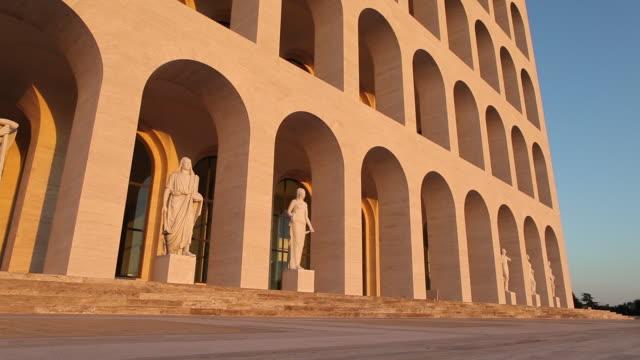 ws man walking past palazzo della civilta italiana / rome, italy - cultura italiana video stock e b–roll