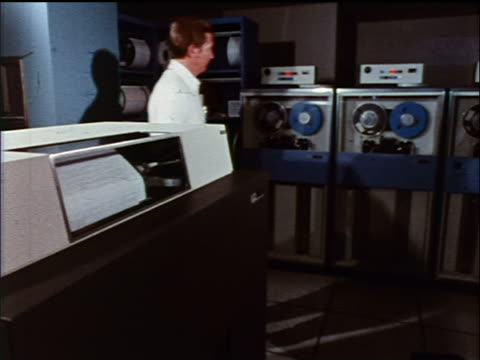 1973 man walking past tape drives to look at computer printout on printer / industrial