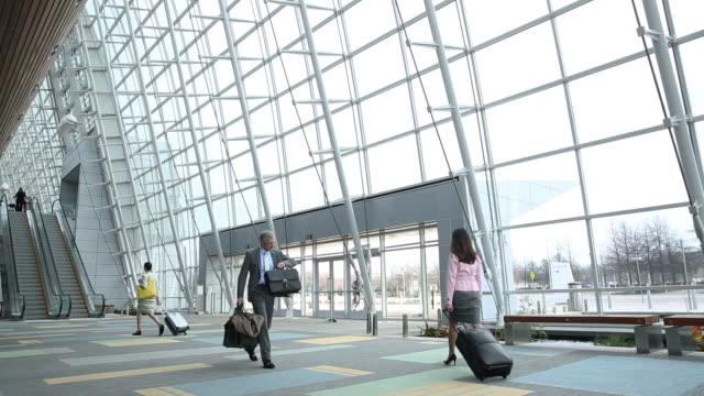 vidéos et rushes de man walking through airport terminal - aéroport