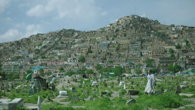 man walking through cemetery in karte sakhi district, kabul - kabul stock-videos und b-roll-filmmaterial