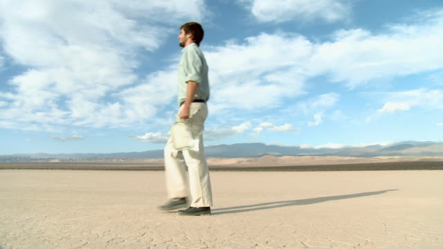 vidéos et rushes de man walking through desert landscape with bottle of water - limite