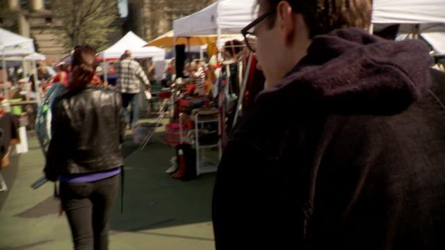 stockvideo's en b-roll-footage met ts ms man walking through flea market, new york city, new york, usa - rommelmarkt