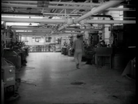 1944 Man walking through Goodyear Synthetic Rubber plant / Los Angeles, California, United States