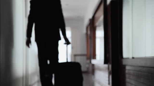 ws man walking through hallway with pulling suitcase on wheels / port de soller, mallorca, baleares, spain - bagaglio video stock e b–roll