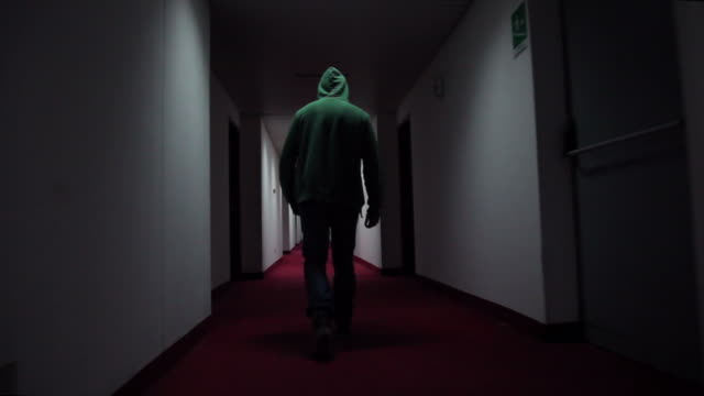 man walking through hotel corridor - hooded top stock videos & royalty-free footage
