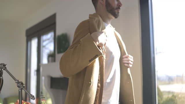 man walking through living room and putting on his coat - t shirt stock videos & royalty-free footage