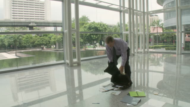 MS PAN ZI Man walking through lobby, papers dropping out of briefcase on floor / Bangkok, Thailand