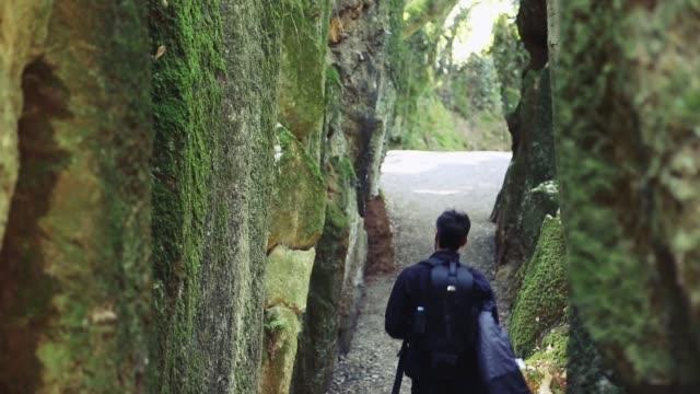Man walking through nature and between rocks
