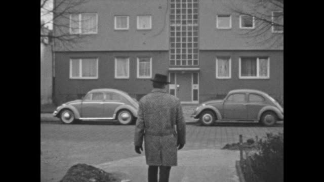 vídeos de stock e filmes b-roll de man walking through neighborhood on a sunday in western berlin, many shots of new built houses, example of the rebuilding of the city after wwii and... - milagres