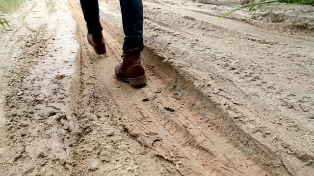 man walking through the mud full hd. - boot stock videos & royalty-free footage