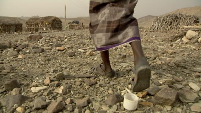 man walking through village - äthiopien stock-videos und b-roll-filmmaterial