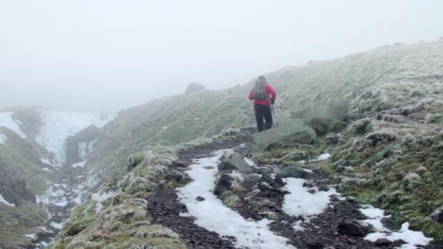 ws man walking through winter mountain landscape - hiking pole stock videos & royalty-free footage