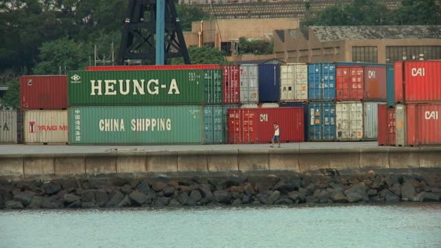 vídeos de stock e filmes b-roll de ws man walking through yard with stacks of shipping containers / hong kong, china - grupo médio de objetos