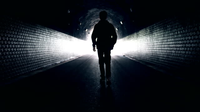 man walking to light in dark tunnel - speranza video stock e b–roll