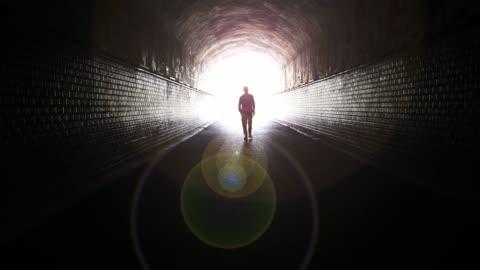 vídeos y material grabado en eventos de stock de hombre caminando a la luz en túnel oscuro - pasillo característica de edificio