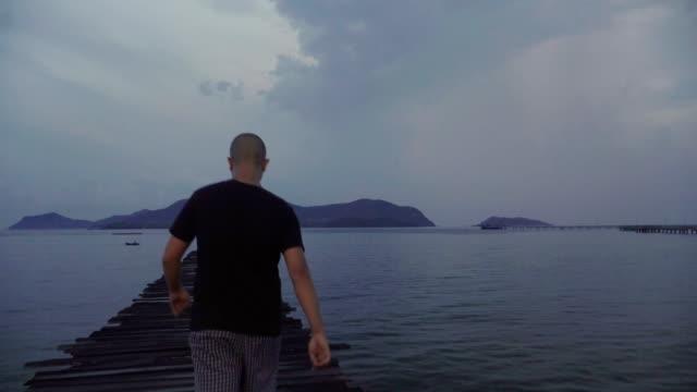 Mann zu Fuß zum Meer mit Holzbrücke