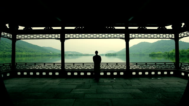 A man walking to the lake Under the old pavilion