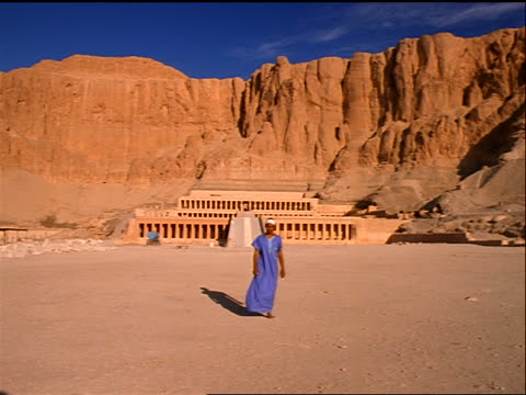 man walking toward camera from temple at foot of cliff / mortuary temple of queen hatshepsut, egypt - tempio di hatshepsut video stock e b–roll
