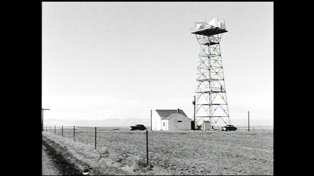 vidéos et rushes de man walking toward relay/transmitting tower on top of a snowy hill; landscape view of hills and radio building in the foreground; relay tower against... - 1940 1949