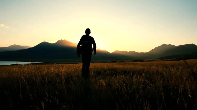 vídeos de stock e filmes b-roll de man walking toward sunlight in autumn plain - ir em frente