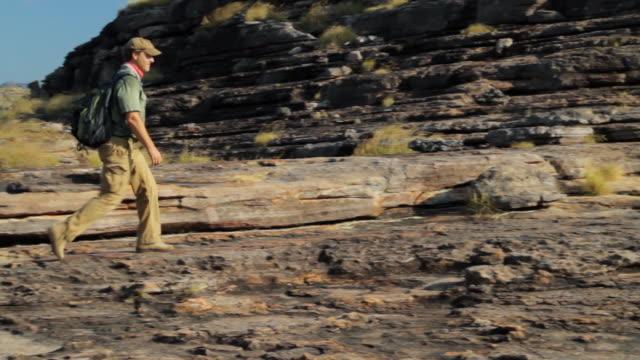 ms pan man walking towards edge of cliff / northern territory, australia - wiese stock videos & royalty-free footage