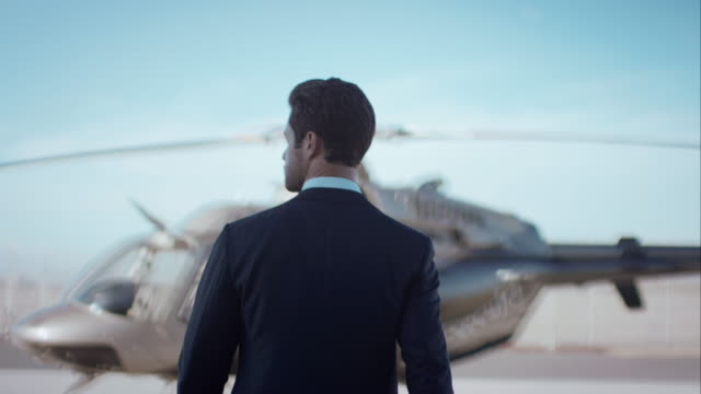 man walking towards helicopter - luxury stock videos & royalty-free footage