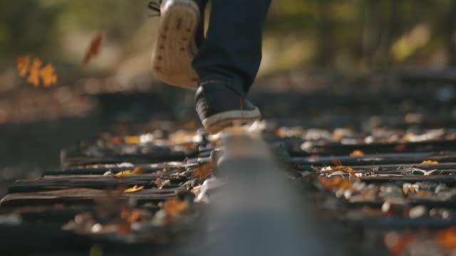 vídeos de stock, filmes e b-roll de man walking tracks as leaves fall all around, super slow motion - transporte ferroviário