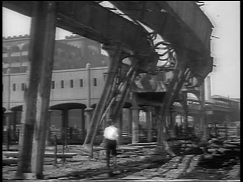 b/w 1934 man walking under destroyed el tracks after chicago stockyard fire / newsreel - 1934 stock videos & royalty-free footage