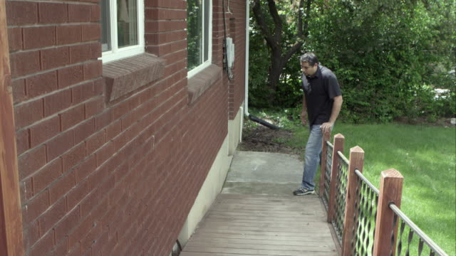 Man walking up home ramp with a limp.