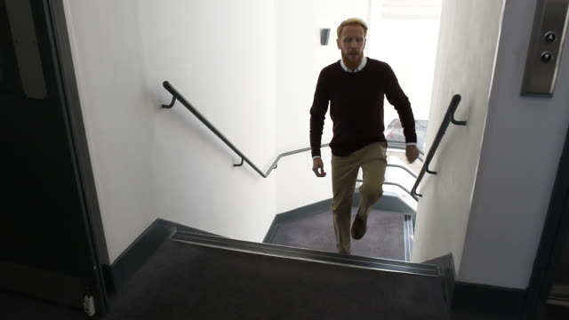 vídeos de stock e filmes b-roll de man walking up stairs in office - degraus