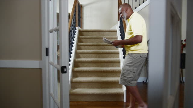 MS Man walking up stairs with coffee and newspaper / Bothell, Washington State, USA