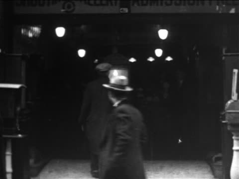 b/w 1906 man walking up to ticket booth of shooting gallery / new york city / newsreel - 1906 stock-videos und b-roll-filmmaterial