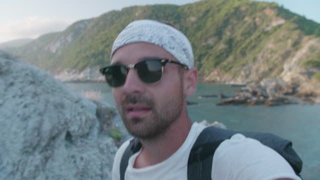 vídeos de stock, filmes e b-roll de a man walking while filming a selfie portrait, lifestyle in greece. - evitar os outros