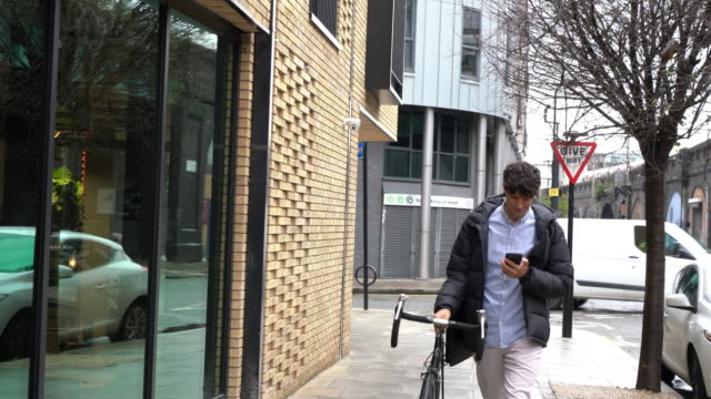man walking with bicycle and looking at mobile phone - warm clothing stock videos & royalty-free footage