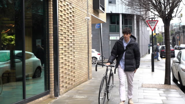 man walking with bicycle on street looking at mobile phone - warm clothing stock videos & royalty-free footage