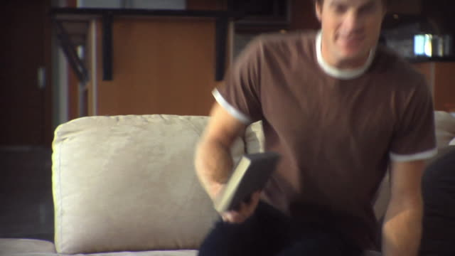 SLO MO Man walking with holding book, sitting on sofa, reading / Whistler, British Columbia, Canada