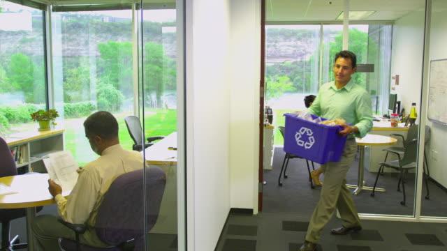 ms man walking with recycle bin in office hallway, austin, texas, usa - ansvarsfullt företagande bildbanksvideor och videomaterial från bakom kulisserna