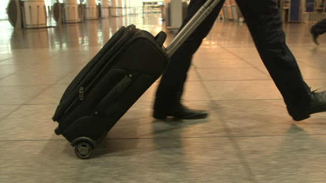 man walking with suitcase at airport - wheeled luggage stock videos and b-roll footage