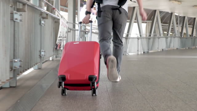 man walking with travel bag in the airport terminal. - urgency stock videos & royalty-free footage