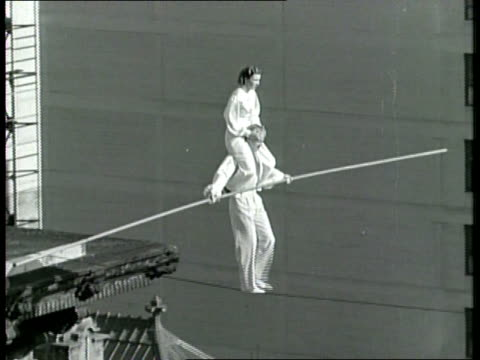 A man walks a tightrope with his wife on his shoulders across Grand Avenue from the Biltmore Hotel in Los Angeles /