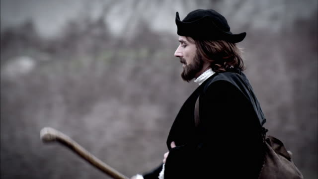 a man walks across a field carrying a backpack and walking stick. - historical reenactment stock videos & royalty-free footage