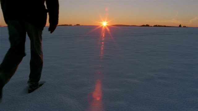 vídeos y material grabado en eventos de stock de a man walks across a snow-covered plain. - pisada