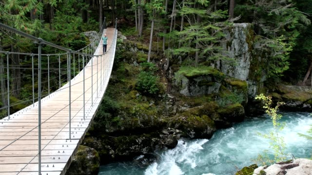 man walks across a suspension bridge - suspension bridge stock videos & royalty-free footage