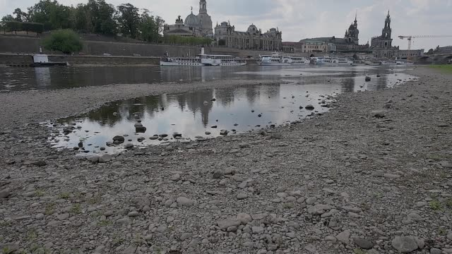 a man walks across an exposed portion of the elbe river during hot weather on august 8 2018 in dresden germany a heat wave and dry spell is... - 低い点の映像素材/bロール