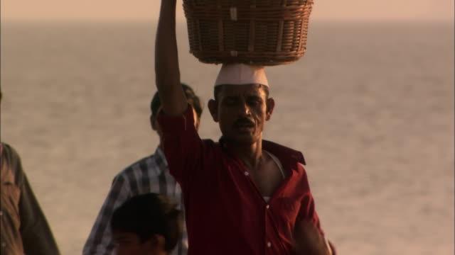 man walks across beach carrying basket on head mumbai available in hd. - mumbai stock videos & royalty-free footage