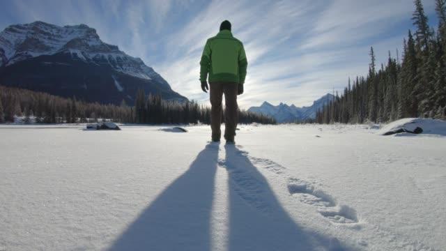 vídeos de stock e filmes b-roll de man walks across snowy terrain, in mountains - rasto forma