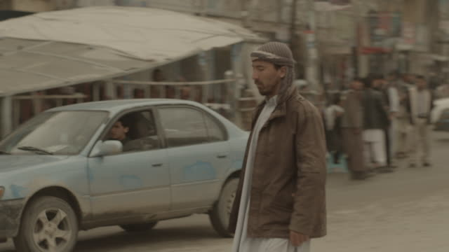 man walks across the street with armed forces standing near - kabul stock videos & royalty-free footage