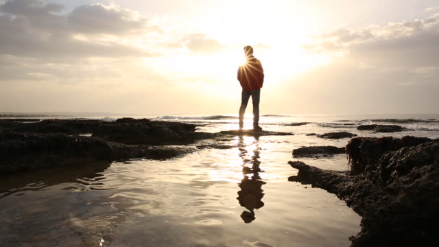 man walks across tidal pools to sea edge, watches sunrise - only mature men stock videos & royalty-free footage