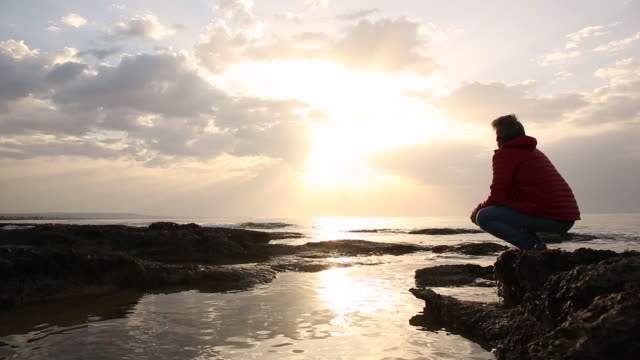 man walks across tidal pools to sea edge, watches sunrise - tidal pool stock videos and b-roll footage
